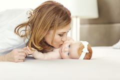 A happy grandmother kissing baby grandson on the bed. royalty free stock photography