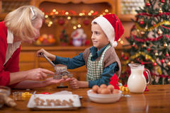 Happy grandmother and little boy in kitchen preparing Xmas cooki. Grandmother and little boy baking Christmas cakes in the kitchen Royalty Free Stock Photography