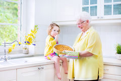 Happy grandmother and little girl baking a pie in a white kitche. Happy beautiful great grandmother and her adorable granddaughter, curly toddler girl in Royalty Free Stock Photography