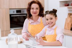 happy grandmother with little granddaughter cooking together and looking royalty free stock photos