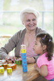 Happy grandmother looking away while granddaughter blowing stacked alphabet blocks in house Royalty Free Stock Photos
