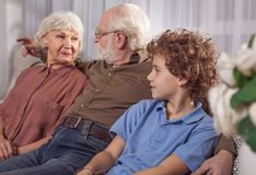 Outgoing grandparents and glad kid speaking Stock Photo