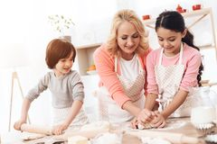 Happy grandmother together with little happy grandchildren knead dough for cookies in kitchen. Grandmother with her grandchildren cooks pastries in kitchen royalty free stock image
