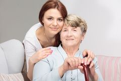 Grandmother with walking stick and hugging her smiling daughter royalty free stock photo