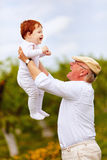 Happy grandpa playing with infant grandson in spring garden. Happy grandpa playing with cute infant grandson in spring garden Stock Photos