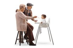 Happy grandparents feeding a baby in a chair. Isolated on white background royalty free stock photo