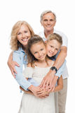 Grandparents with grandchildren hugging. Happy grandparents with grandchildren hugging and smiling at camera isolated on white stock photos