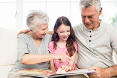 Happy grandparents with granddaughter reading a book Royalty Free Stock Image