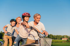 Grandparents helping children ride bicycle stock image