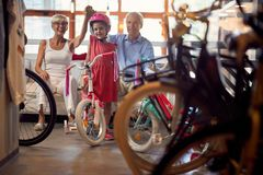 Grandparents shopping new bicycle for little girl. Happy grandparents shopping new bicycle for little girl stock photography