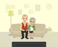 Happy grandparents sitting at home and watching a tv Stock Photos