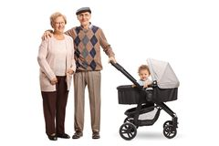 Happy grandparents standing with a pushchair and their grandson stock photos