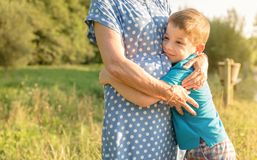 Happy grandson hugging to his grandmother outdoors Stock Photo