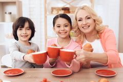 Happy granny with grandson and granddaughter clink cups of tea at kitchen. Beautiful grandmother with her grandchildren at tea party Stock Image