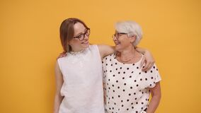 Happy granny and her granddaughter hugging. Isolated on orange background