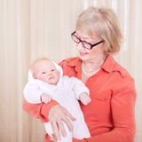 Happy granny holding newborn child. Happy granny holding newborn kid at home, enjoying sweet little grandchild, hugging with love, family happiness concept Royalty Free Stock Photos