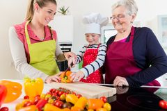 Granny showing old family recipe to grandson and daughter. Happy granny showing old family recipe to grandson and daughter stock photo