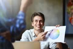 Happy graphic designer holding color diagram in his hand royalty free stock images