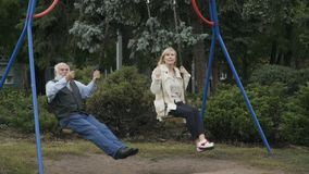 Two adult people swings in slowmotion stock video footage