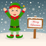 Happy Green Elf & Merry Christmas Sign. A merry Christmas greeting card with a happy green elf smiling in a snowy scene with a merry Christmas wooden sign. Eps Royalty Free Stock Photos