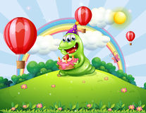 A happy green monster celebrating his birthday at the hilltop Stock Image