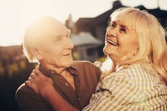 Happy grey-haired hugging blithesome couple having fun royalty free stock photography