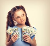 Happy grimacing doubt thinking kid girl holding money in the han. Ds and looking up on empty copy space background. Vintage toned portrait royalty free stock image