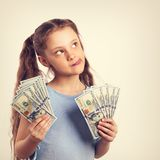 Happy grimacing fun thinking kid girl holding money in the hands. And looking up on empty copy space. Toned portrait vintage Royalty Free Stock Photography