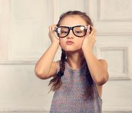 Happy grimacing kid girl in fashion glasses with fun emotional f. Ace looking on blue studio background in colorful blouse. Closeup toned portrait royalty free stock images