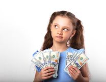 Happy grimacing thinking kid girl holding money in the hands and. Looking up on white background with empty copy space Stock Photos