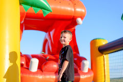 Happy grinning little boy at a fair. Or a kids playground standing in front of an inflatable jumping castle in the shape of a hippo Stock Photo