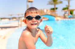 Happy grinning young boy at a swimming pool. Sitting on the edge wearing his goggles and costume as he enjoys the summer sun on vacation Royalty Free Stock Photo