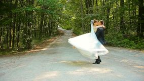 Happy groom and beautiful bride in white dress dancing in the green forest stock video footage