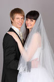 Happy groom and bride embrace in studio Stock Photo