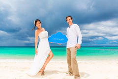 Happy groom and bride having fun on the sandy tropical beach. We Stock Photography