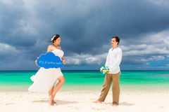 Happy groom and bride having fun on the sandy tropical beach. We Royalty Free Stock Image