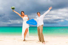 Happy groom and bride having fun on the sandy tropical beach. We Stock Images