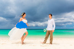 Happy groom and bride having fun on the sandy tropical beach. We Royalty Free Stock Photos