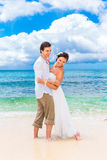 Happy groom and bride having fun on the sandy tropical beach. We Stock Photo