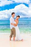 Happy groom and bride having fun on the sandy tropical beach. We Stock Photo