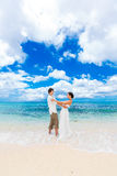Happy groom and bride having fun on the sandy tropical beach. We Royalty Free Stock Photo