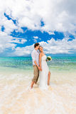 Happy groom and bride having fun on the sandy tropical beach. We Royalty Free Stock Images