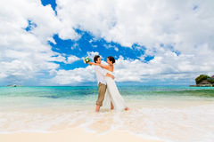 Happy groom and bride having fun on the sandy tropical beach. We Stock Photos