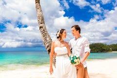 Happy groom and bride having fun on the sandy tropical beach. We Stock Image