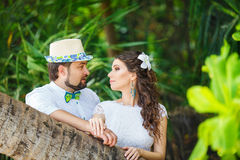 Happy groom and bride having fun in a tropical jungle under the Royalty Free Stock Images