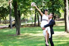 Happy groom with bride in his arms Royalty Free Stock Photo