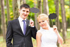 Happy Groom and Bride in a park with signs Royalty Free Stock Photos
