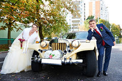 Happy groom and bride about retro limousine Stock Photography