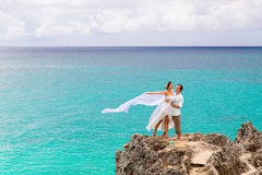 Happy groom and bride on the rock. Turquoise sea in the backgrou Royalty Free Stock Image