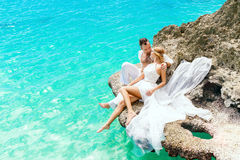 Happy groom and bride on the rock. Turquoise sea in the backgrou Royalty Free Stock Photos